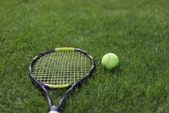 Tennis ball with racket on wet grass after raining Royalty Free Stock Photography