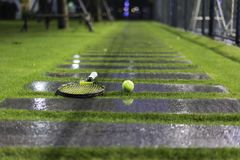 Tennis ball and racket on wet walkway and grass after raining.  Royalty Free Stock Photos