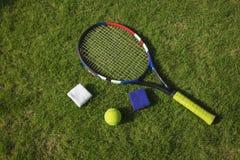 Tennis ball, racket and wristbands on grass field ground under sunlight.  stock photo