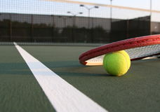 Tennis ball and rackuet. Tennis racket and ball on a tennis court Royalty Free Stock Photo