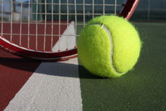 Tennis ball and racquet. On the court Stock Photo