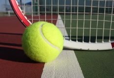 Tennis ball and racquet. On the court Royalty Free Stock Photos
