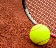 Tennis ball and racquet on a tennis clay court stock photos