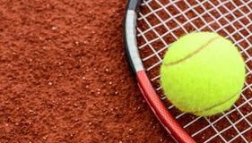 Tennis ball and racquet on clay macro shot. Tennis ball and racquet on a tennis clay court royalty free stock photos
