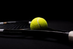 Tennis ball and racquet. Close-up view of tennis ball and racquet  on black Stock Photo