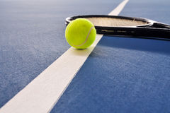 Tennis ball and racquet on a court line Royalty Free Stock Photos
