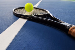 Tennis ball and racquet on a court line Royalty Free Stock Images