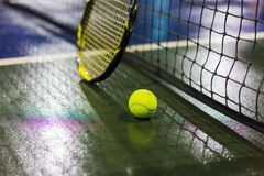 Tennis ball, racquet and net on wet ground after raining.  Royalty Free Stock Images