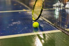 Tennis ball, racquet and net on wet ground after raining.  Royalty Free Stock Photo