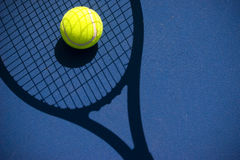 Tennis ball in a racquet shadow Stock Photos