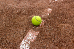 Tennis ball on a red court Stock Images