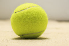 Tennis ball in the sand.  Stock Photos