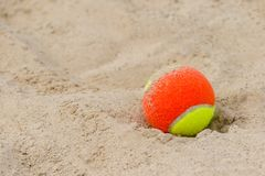 Tennis ball on the sand at the beach close up royalty free stock photography
