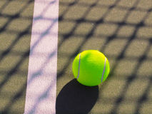 Tennis ball with shadow of net. Tennis ball on the court with shadow of net Stock Photography