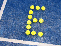 Tennis ball in shape of letter E on a blue artificial grass court Royalty Free Stock Photography