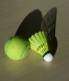 Tennis ball and shuttlecock with shadows. On the table Stock Image