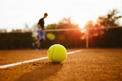 Tennis ball and silhouette of player on a clay court Stock Photography