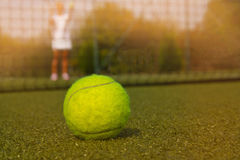 Tennis ball and silhouette of tennis player in sammer day. Tennis ball and silhouette of tennis player match Stock Photography