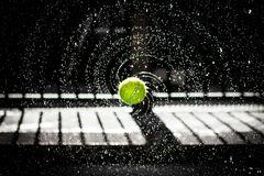 Tennis ball splashing water Stock Photo