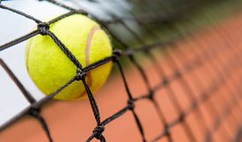 Tennis ball stuck on the net Stock Photos