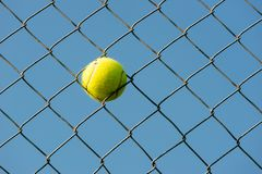 Tennis ball stuck in steal wire net horizontal shot royalty free stock photography