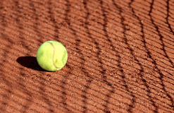 Tennis ball on a tennis clay court with net shadow Stock Image