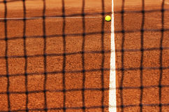 Tennis ball on tennis court. View through net. Focus on ball and part of court line. Corner of service field. Copy space available Royalty Free Stock Photos