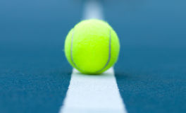 Tennis ball on tennis court with white line. Close-up tennis ball on tennis court with white line Royalty Free Stock Photo