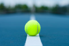 Tennis ball on tennis court with white line Stock Images