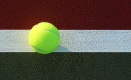 Tennis Ball on tennis court. Yellow tennis ball on green and red tennis court foul line royalty free stock photo