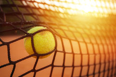 Tennis ball in the tennis net. Tennis ball hitting the tennis net on clay court Royalty Free Stock Photography