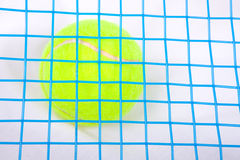 Tennis ball under a raquet Royalty Free Stock Photo
