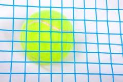 Tennis ball under a raquet. Close up of yellow tennis ball under a tennis raquet Royalty Free Stock Photo