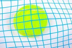 Tennis ball under a raquet. Close up of yellow tennis ball under a tennis raquet royalty free stock photos
