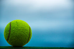 A tennis ball. On a wall against a blue sky stock image