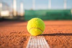 Tennis ball on white line. Small tennis ball lying on white line on tennis court on sunny day Royalty Free Stock Photos