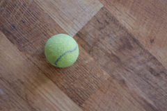 Tennis ball on a wood floor Stock Photos