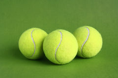 Tennis balls. Four tennis ball on a green background Royalty Free Stock Photos