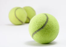 Tennis Balls. Three tennis balls and one sitting close out in the front Stock Photo