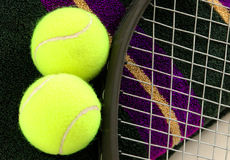 Tennis Balls. Two tennis balls, towel, and a racket royalty free stock image