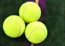 Tennis Balls. Three tennis balls on a purple and gold towel stock image