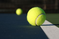 Tennis balls. On a modern blue court Royalty Free Stock Image