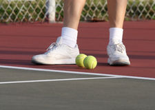Tennis Balls. Couple tennis balls standing by a pair of feet royalty free stock photos