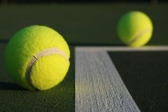 Tennis Balls. Two tennis balls in a court, one in focus and one out of focus Stock Photo