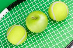 Tennis balls with apple and ra. Two tennis balls with apple and racket on green background Stock Photos