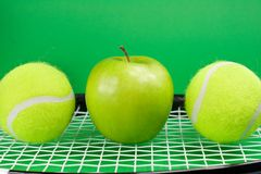 Tennis balls with apple and racket. Two tennis balls with apple and racket on green background Stock Photography
