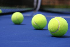 Tennis Balls on Blue Court. With net background Royalty Free Stock Photography