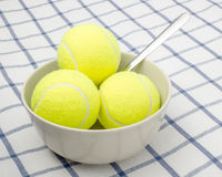 Sports instead of food. Tennis balls are in a bowl instead of ice cream royalty free stock photos