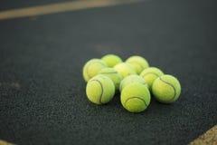 Tennis balls. Bright yellow tennis balls on a dark green tennis court sports entertainment equipment stock photo