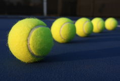 Tennis balls on the court. Tennis balls lined up on the court Stock Photo